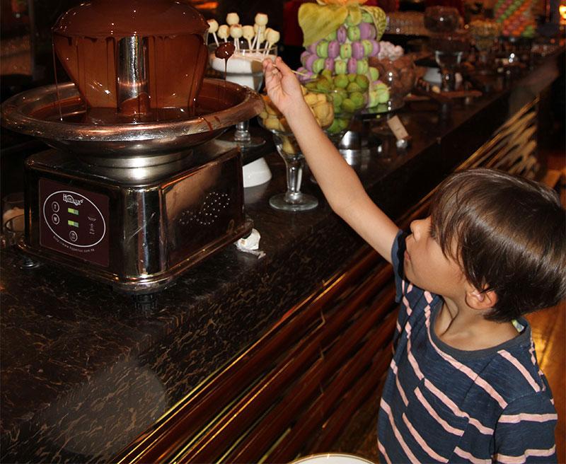 kid having fun at the chocolate fountain hotel Kempinski Jakarta