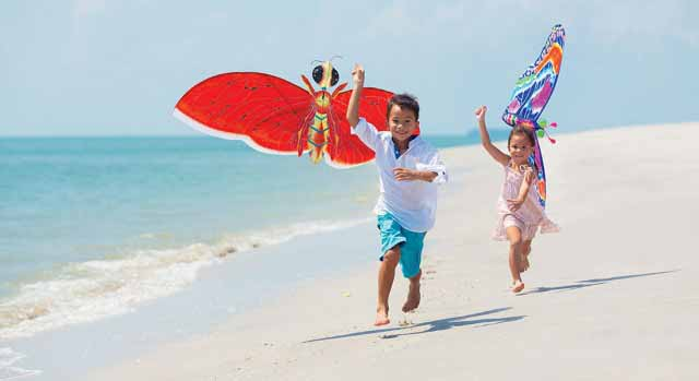 kids playing at the beach at kid friendly hotel four seasons langkawi malaysia